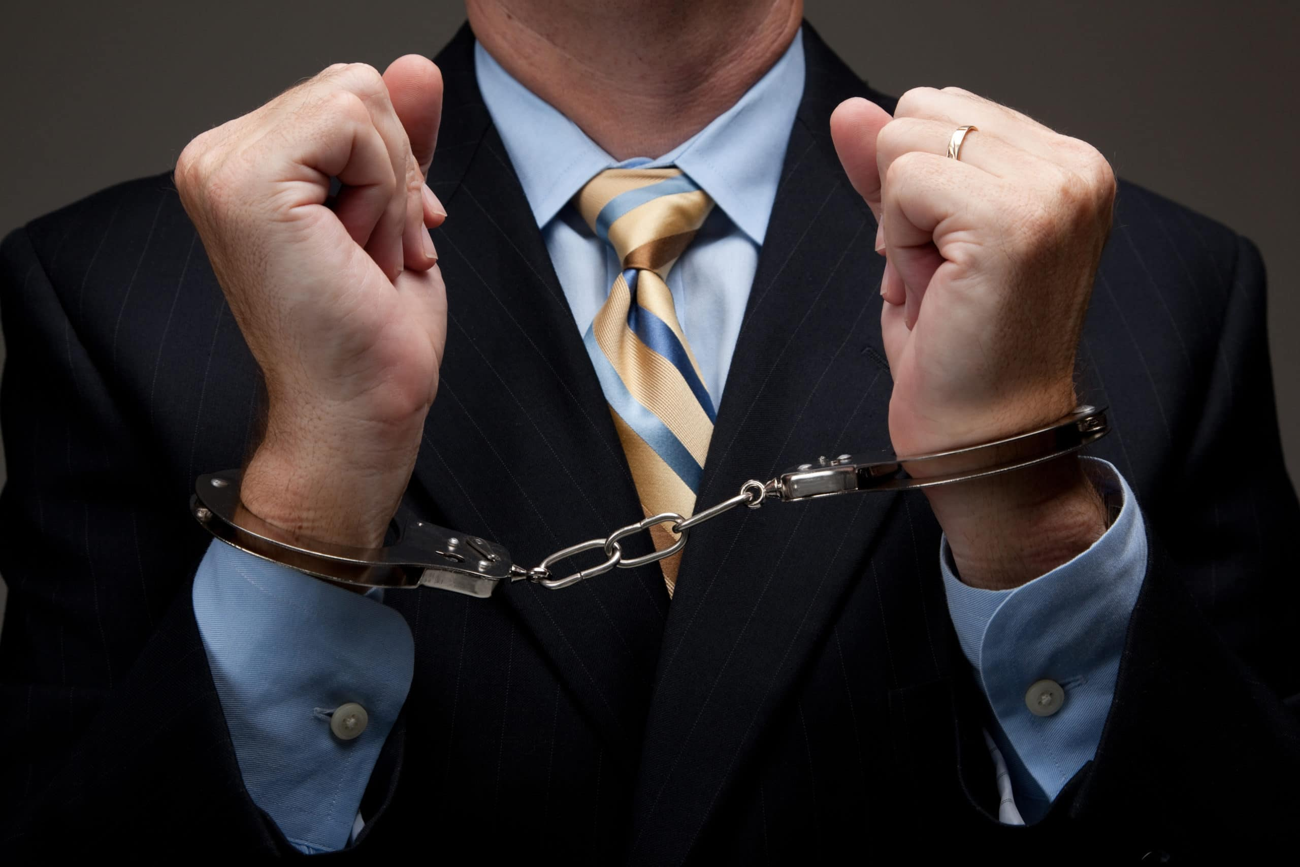 White,Collar,Criminal,In,A,Business,Suit,And,Handcuffs